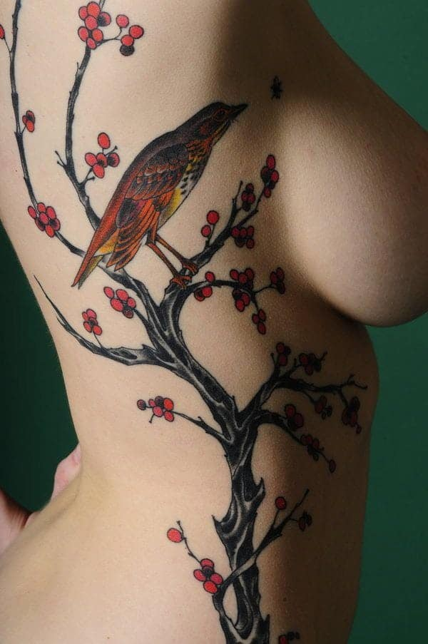 a2508434b If you are a nature lover than you are going to love this bird tattoo which  totally compliments the cherry blossoms.
