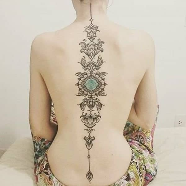 1df548b7bbb4d ... spine, these flowers and leaves tattoo works well with your femininity.  See that blue-green color at the center? It's the eye of every woman's soul.